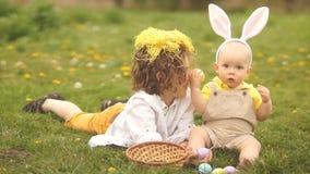 2 брать, подросток и младенец отдыхают в парке на glade Концепция пасхи, уши зайчика, корзина пасхи и яйца видеоматериал
