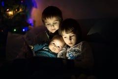 3 брать, сидя дома на софе в живущей комнате, чтение Стоковая Фотография RF