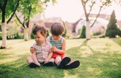 2 брать сидя совместно на траве Стоковые Изображения RF