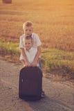 2 брать с чемоданом на дороге в лете на заходе солнца Стоковая Фотография RF