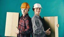 Брат-близнецы в оранжевых и белых шлемах показывают большие пальцы руки вверх Стоковые Изображения
