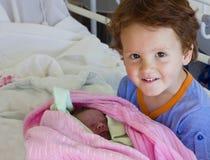 Брат встречая newborn сестру в больнице Стоковые Изображения