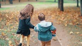 Брат заднего взгляда милый и мальчик и девушка сестры бежать держащ руки с их игрушками через переулок осени замедляют mo видеоматериал