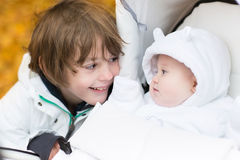 Брат играя при его сестра младенца сидя в прогулочной коляске Стоковое Изображение RF