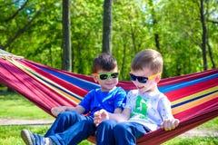 Брат и мальчик ослабляя в гамаке на каникулах Стоковые Изображения