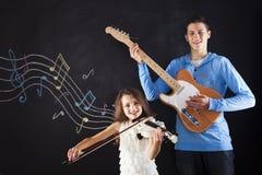 Брат и сестра делая музыку Стоковая Фотография