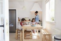 Брат и сестра делая домашнюю работу в кухне пока мама варит Стоковая Фотография RF