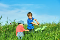 Брат и сестра играя в поле с модельным самолетом Стоковые Фотографии RF