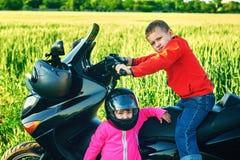Брат и сестра играя на мотоцикле Стоковые Фотографии RF