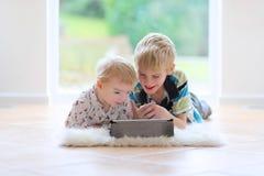 Брат и сестра играя с ПК таблетки внутри помещения Стоковое Изображение RF