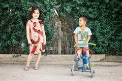 Брат и сестра играя с трициклом в милом традиционном платье стоковые изображения