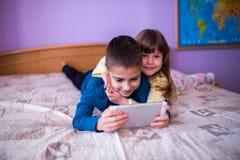 Брат и сестра имея потеху с таблеткой дома Стоковое Фото