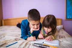 Брат и сестра имея чертеж потехи на кровати Стоковая Фотография