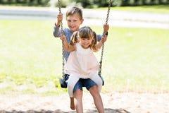 Брат и сестра наслаждаясь на качании в парке Стоковое фото RF
