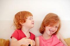 Брат и сестра околпачивая вокруг на кровати стоковое изображение rf