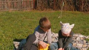 Брат и сестра осматривают earthworms сидя на лужайке в задворк дома сток-видео