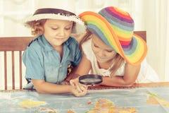 Брат и сестра рассматривают карту мира с увеличивать Стоковая Фотография RF