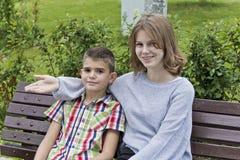 Брат и сестра сидят на стенде стоковые изображения rf