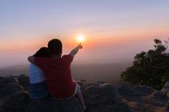 Брат и сестра сидя на утесе и видят заход солнца совместно Стоковые Изображения