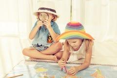Брат и сестра смотря карты мира Стоковые Фото