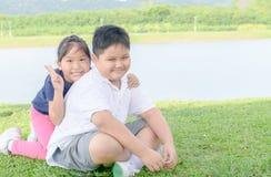 Брат и сестра усмехаются и смотрятся камеру Стоковые Изображения RF