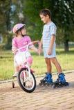 Брат и сестра outdoors ехать велосипеды и ролик Стоковая Фотография RF