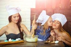 Брат и сестры в шляпах шеф-повара подготавливая тесто стоковое фото