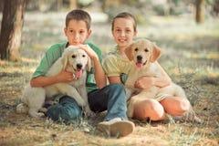 Брат сестры подростка сцены щенка Retriever симпатичный наслаждается представить каникулы временени с собакой белым labrador цвет стоковая фотография
