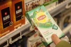 Бренд Lipton дозы чая в руке на супер супермаркете u стоковые фотографии rf