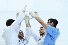 Бригада хирургов поднимая их руку Стоковое Фото