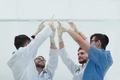 Бригада хирургов поднимая их руку Стоковое фото RF