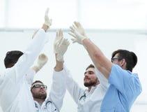 Бригада хирургов поднимая их руку Стоковые Фото