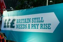 Британия заслуживает подъем оплаты - закончите марш протеста крышки теперь Стоковое фото RF