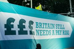 Британия заслуживает подъем оплаты - закончите марш протеста крышки теперь Стоковые Фотографии RF