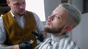 Брить бороды Волосы стороны ` s людей вырезывания парикмахера с триммером бороды на парикмахерскае сток-видео