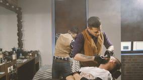 Брить процесс бород в парикмахерскае Мастер делает клиента бороды стрижки с винтажной прямой бритвой сток-видео