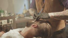 Брить процесс бород в парикмахерскае Мастер делает клиента бороды стрижки с винтажной прямой бритвой видеоматериал