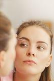 Брови женщины tweezing общипывая с щипчиками Стоковые Изображения