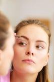 Брови женщины tweezing общипывая с щипчиками Стоковые Фотографии RF