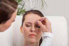 Бровь женщины Youtg красивая общипывая щипчики наблюдает волосы стоковые изображения