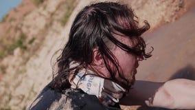 Бродяга в грязных одеждах и длинных волосах собирает воду от грязной лужицы в пустыне Выживание в трудных условиях сток-видео