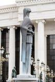 Бронзовая скульптура стилизованной женской диаграммы держа розарий sy Стоковые Фотографии RF