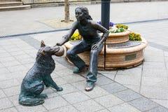 Бронзовая статуя девушки играя с ее собакой рядом с рекой Дунаем Стоковое Изображение RF