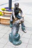 Бронзовая статуя девушки играя с ее собакой рядом с рекой Дунаем Стоковые Фото