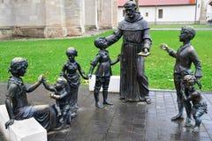 Бронзовая статуя женщины, священника и детей стоковое изображение