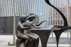 Бронзовая статуя играющего Со рояля стоковое фото rf