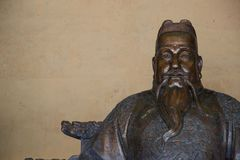 Бронзовая статуя китайского человека со шляпой и бородой стоковое изображение rf