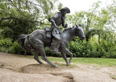 Бронзовый ковбой на скульптуре лошади, пионерской площади, Далласе Стоковое Изображение