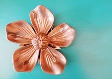 Бронзовый орнамент цветка на предпосылке бирюзы стоковое фото