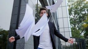 Бросать бизнесмена завертывает документы в бумагу в воздух и празднует успех на предпосылке офисного здания Свобода, успешная акции видеоматериалы